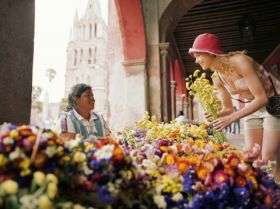 Expat woman buying flowers from local Mexican in San Miguel de Allende – Best Places In The World To Retire – International Living