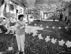 Woman hanging decorations on street in Ajijic, 1950s – Best Places In The World To Retire – International Living