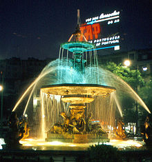 1968 TAP airline commercial in lights behind  the fountain in  Rossio Square, Lisbon, Portugal – Best Places In The World To Retire – International Living
