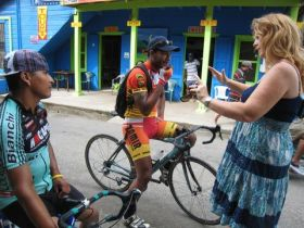 Macarena Rose in San Ignacio, Cayo district Belize talking to bicylist downtown – Best Places In The World To Retire – International Living