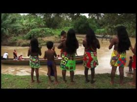 Embera Indians in Panama watch tourist ride a native cayco dugout canoe – Best Places In The World To Retire – International Living