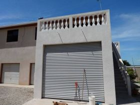 Hurricane shutters on the garage on a home in Corozal, Belize – Best Places In The World To Retire – International Living
