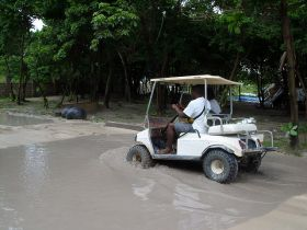 golf cart drives through flooded street during the rainy season Ambergris Caye, Belize – Best Places In The World To Retire – International Living