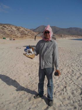 Man collecting garbage on beach in Baja California Sur
