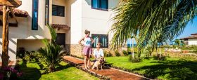 Pedasi home outside view with woman, man, and dog – Best Places In The World To Retire – International Living