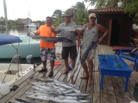 Placencia, Belize, three men holding fish on a dock – Best Places In The World To Retire – International Living