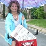 Anne-Michelle Wand Bocas Del Toro, Panana on bike with umbrella – Best Places In The World To Retire – International Living